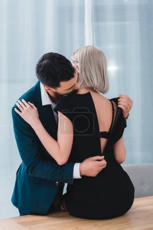 businessman taking off black dress from sexy female colleague in office