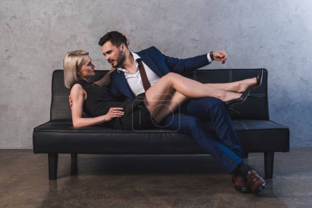 seductive young couple hugging and looking at each other in foreplay on sofa