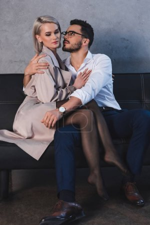 beautiful seductive young couple hugging on sofa in office