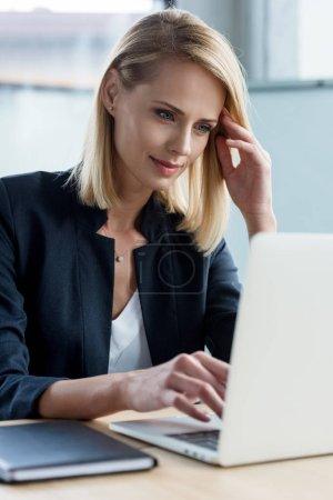 Photo pour Femme d'affaires blonde souriante utilisant l'ordinateur portable au lieu de travail - image libre de droit