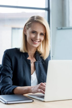 Photo for Beautiful blonde businesswoman using laptop and smiling at camera - Royalty Free Image