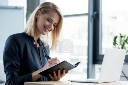 beautiful smiling businesswoman taking notes in notepad at workplace
