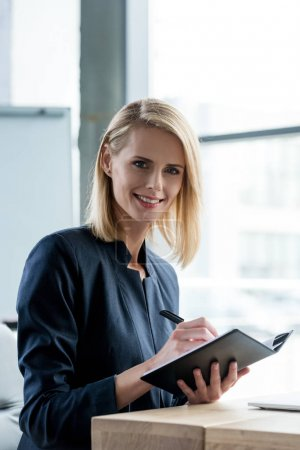 beautiful businesswoman smiling at camera while taking notes in notebook
