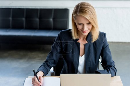 high angle view of smiling businesswoman taking notes and working with laptop in office