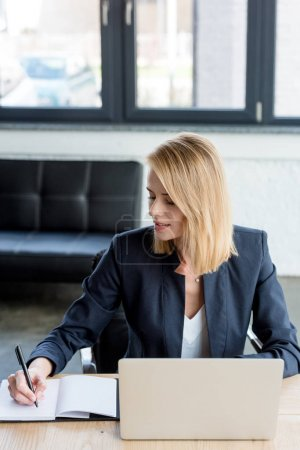 businesswoman taking notes and working with laptop in office