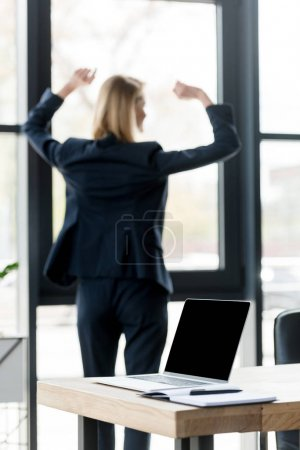 laptop with blank screen on table and businesswoman raising hands near window behind