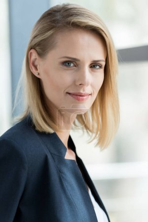 portrait of beautiful blonde businesswoman smiling at camera