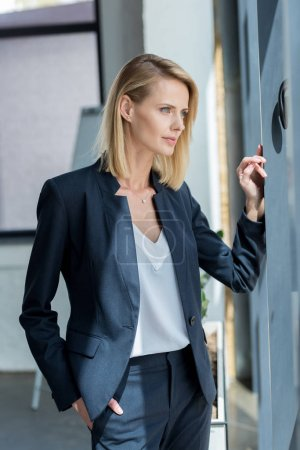 pensive businesswoman standing with hand in pocket and looking away in office
