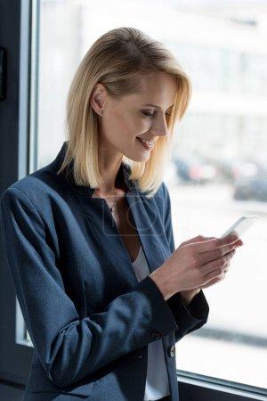 smiling businesswoman in formal wear using smartphone