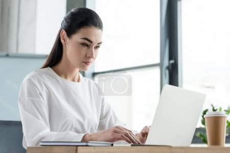 beautiful young businesswoman working with laptop in office