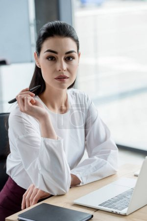 beautiful young businesswoman holding pen and looking at camera in office