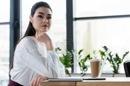 beautiful pensive young businesswoman sitting at table and looking away in office