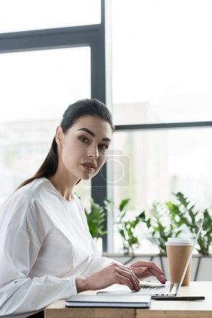 beautiful young businesswoman looking at camera while using laptop in office