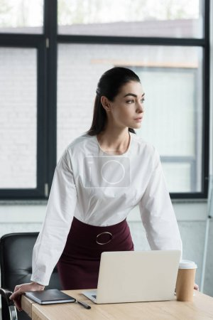 beautiful young businesswoman leaning at table and looking away in office