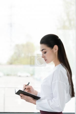 side view of beautiful young businesswoman taking notes in notepad