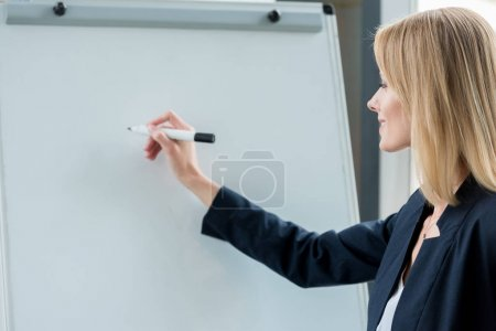 smiling professional businesswoman writing on blank whiteboard