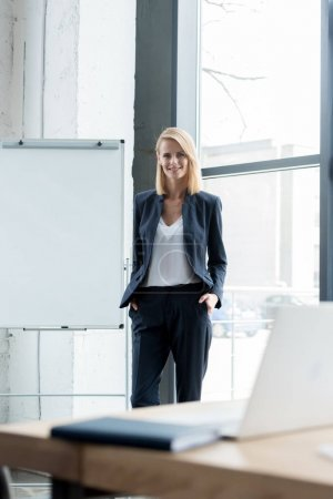 businesswoman standing with hands in pockets and smiling at camera in office