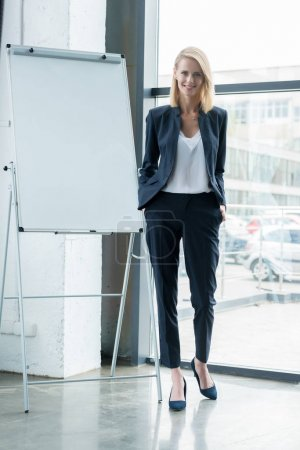 stylish blonde businesswoman standing with hands in pockets and smiling at camera in office
