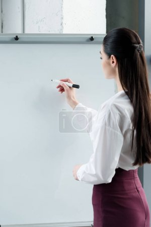 side view of young businesswoman writing on blank whiteboard