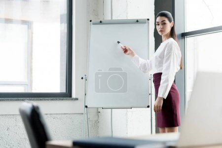 beautiful young businesswoman pointing at whiteboard and looking at camera
