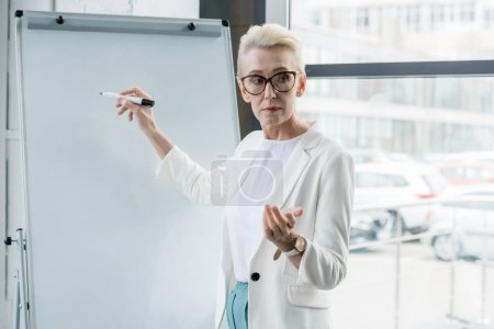 serious senior businesswoman in eyeglasses writing on whiteboard and making presentation in office