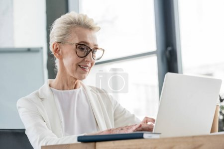 Photo for Smiling senior businesswoman in eyeglasses working with laptop in office - Royalty Free Image