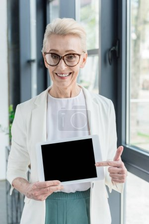 businesswoman in eyeglasses holding digital tablet with blank screen and smiling at camera