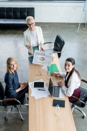 high angle view of businesswomen smiling at camera while working together in office