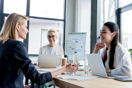 professional businesswomen smiling each other while working together in office
