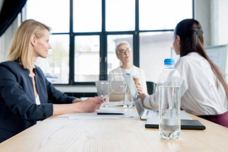 close-up view of bottle of water on table and businesswomen working together in office