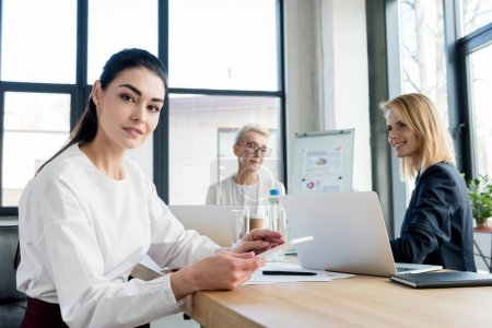 young businesswoman smiling at camera while working with colleagues in office