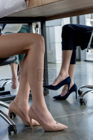 low section of businesswomen in high heeled shoes sitting at table