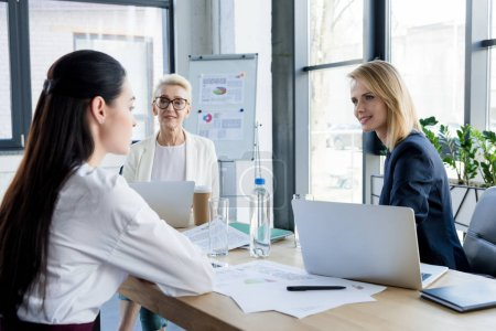 Photo for Smiling beautiful businesswomen talking at meeting in office - Royalty Free Image
