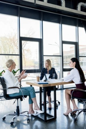 attractive businesswomen discussing and gesturing at meeting in office
