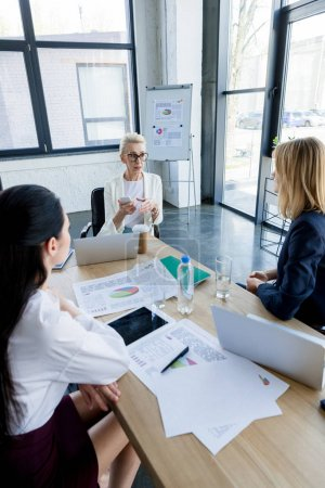 beautiful businesswomen sitting at table with documents during meeting in office