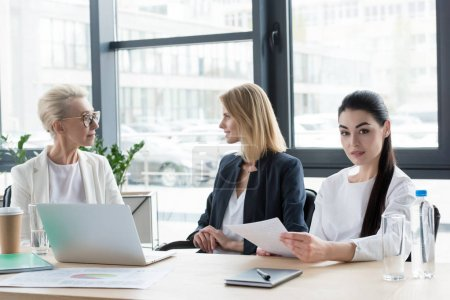 three professional different age businesswomen at meeting in office