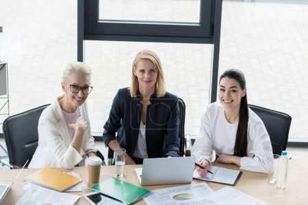 high angle view of beautiful businesswomen looking at camera at meeting in office
