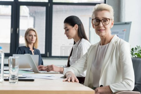 Photo for Beautiful businesswomen sitting at table during meeting in office - Royalty Free Image