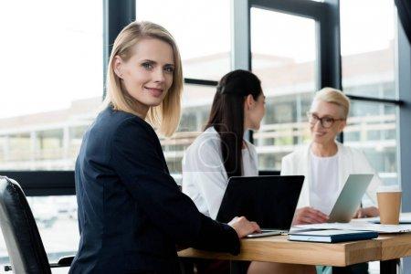 Photo pour Belle femme blonde regardant la caméra lors de réunion tandis que collègues parler au bureau - image libre de droit