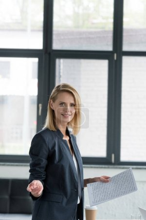attractive businesswoman holding documents and gesturing in office