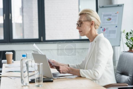 Photo for Side view of attractive senior businesswoman in eyeglasses reading documents in office - Royalty Free Image