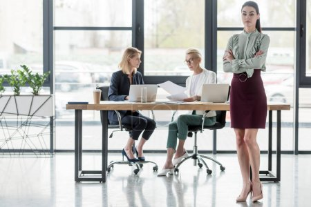 beautiful young businesswoman standing with crossed arms at meeting in office