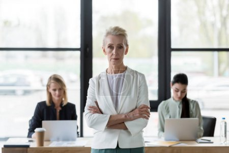 senior beautiful businesswoman standing with crossed arms and looking at camera in office