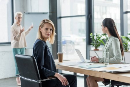beautiful blonde businesswoman looking at camera during meeting in office