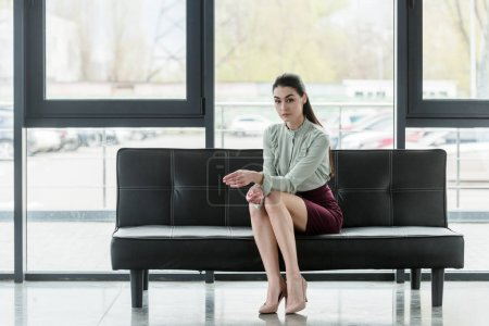 attractive businesswoman sitting on sofa in office