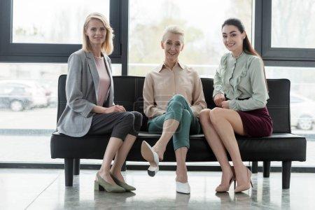 Photo pour Trois belles femmes d'affaires assis sur le canapé dans le bureau et en regardant la caméra - image libre de droit