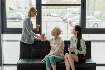 beautiful businesswomen with coffee in paper cups during coffee break in office