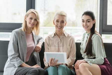 beautiful businesswomen sitting on sofa in office and holding tablet