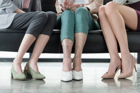 cropped image of businesswomen sitting on sofa in office