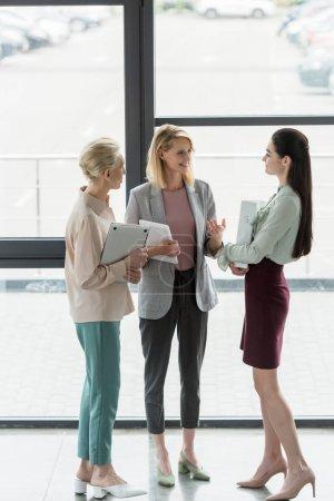 Photo pour Femmes d'affaires belles heureux parler au bureau - image libre de droit